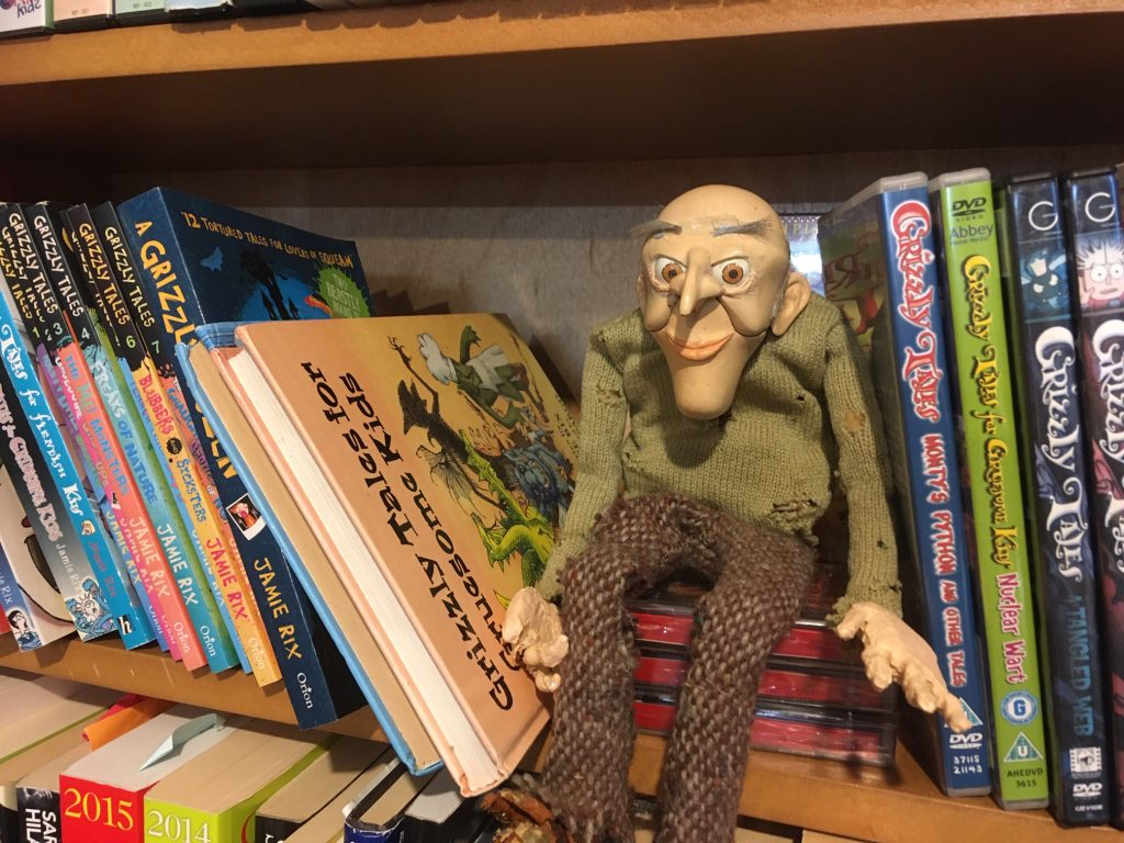 Pupprt of Uncle Grizzly, the storyteller from Grizzly Tales, sits next to the books and DVDs from the series .