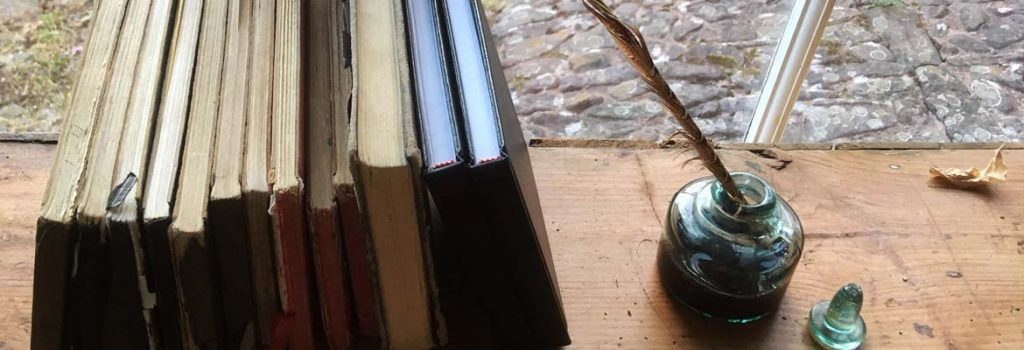 Ink well and quill next to old sketchbooks